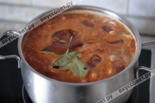 Теперь к мясу добавляем колбасные изделия и овощи с томатной пастой