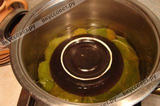 Заливаем водой, чтобы она чуть прикрывала долму, и накрываем тарелкой, чтобы листья не развернулись при варке