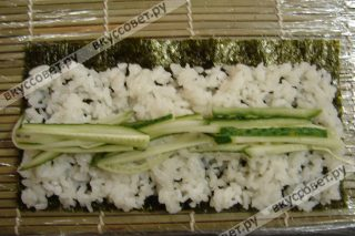 Поверх риса посередине укладываем огурец, не нажимая на него, также можно немного добавить васаби