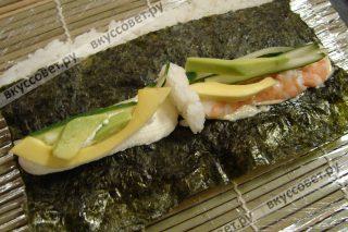 С правой стороны на майонез укладываем порезанные сваренные креветки и огурец, с левой стороны на сыр филадельфия порезанные авокадо