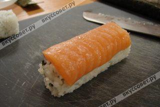 Укладываем лосось и ковриком придаем ему форму ролла