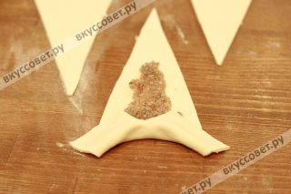 Делаем небольшой надрез в основании треугольника, кладем чайную ложку ореховой начинки и сворачиваем не очень туго от основания до хвоста, немного закругляя